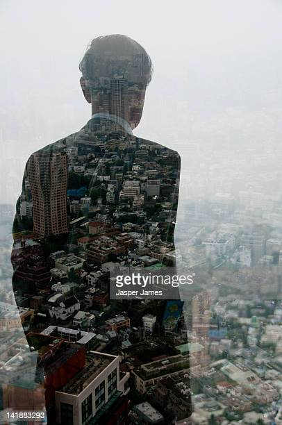 Double exposure of business man looking out of win