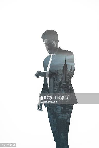 Double exposure of businessman checking the time combined with cityscape