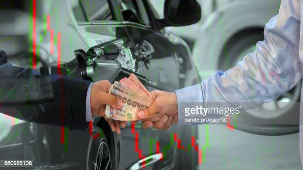 Double exposure of businessman giving money to his partner and blurred Car refueling on a petrol station and World oil price chart , corruption concepts .