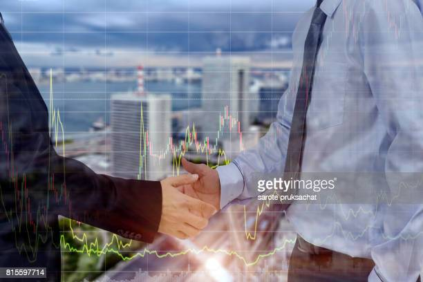 Double exposure of   Businessman groups Handshake for business and dividend yield bar chart on blurred city background. Finance concept.