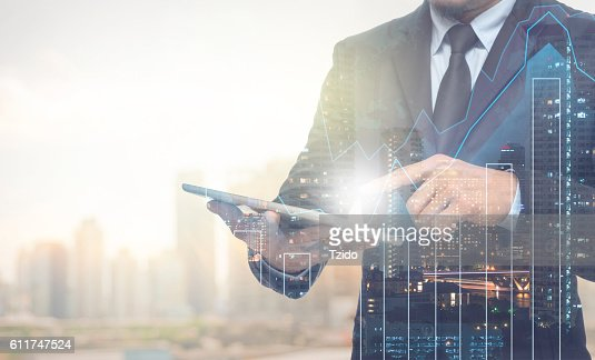 Double exposure of businessman using the tablet with cityscape : Stock Photo