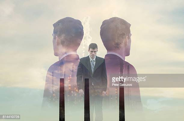Double exposure of businessmen and smoke stacks