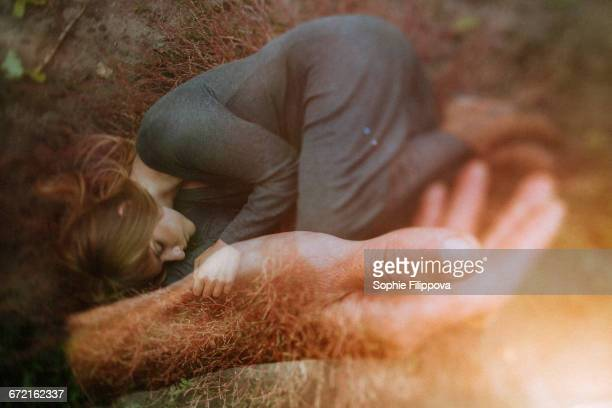 Double exposure of Caucasian woman laying in hand of man