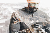Double exposure of city and man using smart tablet. Abstract scene.