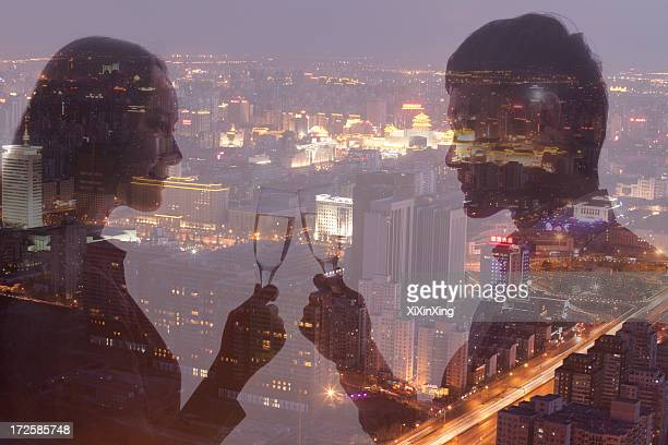 Double exposure of couple toasting with champagne flutes over night cityscape
