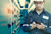 Double exposure of  Engineer or Technician man using smart phone for control electric in switch gear electrical room of oil and gas platform or plant industrial for monitor process, business and indus