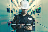 Double exposure of  Engineer or Technician man working with tablet in switch gear electrical room of oil and gas platform or plant industrial for monitor process, business and industry concept.