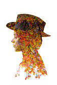 Double exposure of girl portrait wearing hat and autumn leaves