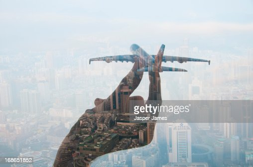 double exposure of hand holding model plane