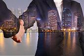 Double exposure of handshake night city, urban and lake