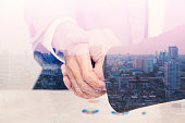 Double exposure of handshake with citi background for investment, devlopment concept.