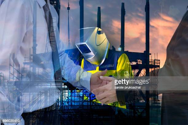 Double exposure of Industrial Worker at the factory and  silhouette construction site sunset.