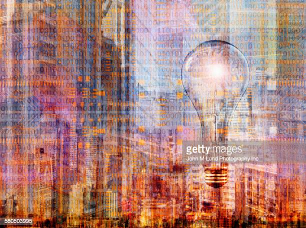 Double exposure of light bulb over cityscape