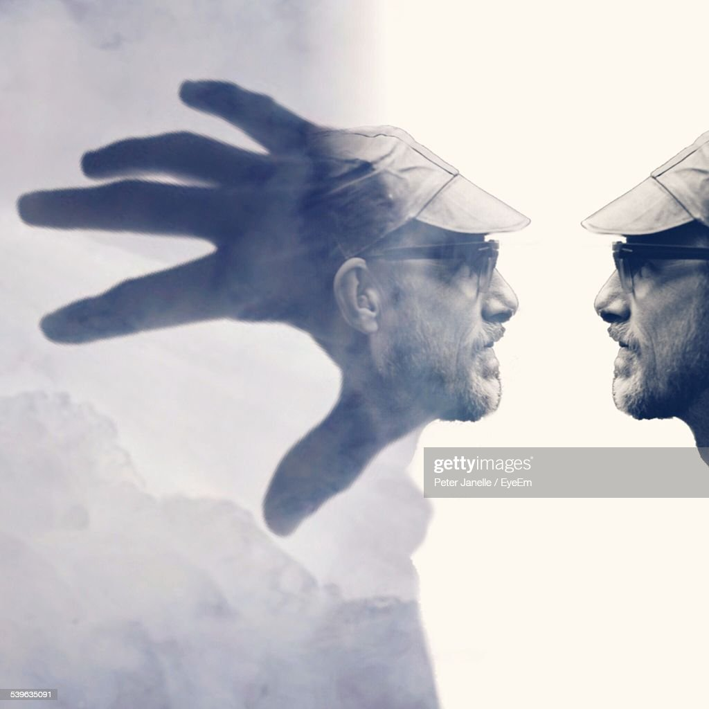 Double Exposure Of Man And Hand Reaching Towards Cloudy Sky