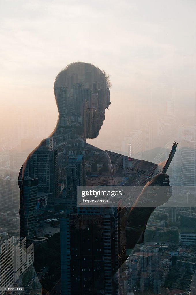 double exposure of man reading newspaper and citys