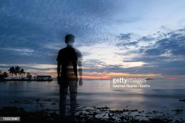 Double Exposure Of Man Standing On Shore At Beach Against Sky During Sunset