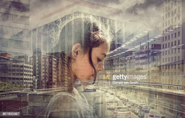 Double exposure of mixed race girl and busy cityscape