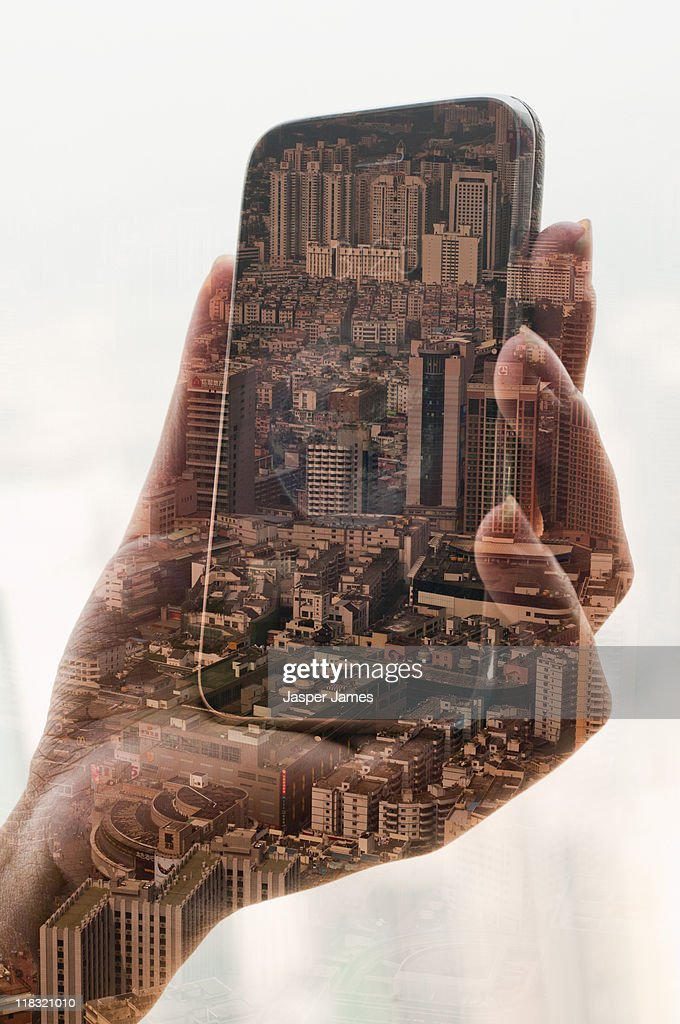 double exposure of mobile phone and cityscape : Stock Photo