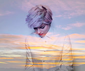 Double exposure of thoughtful girl and sunset