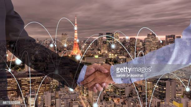 Double exposure of Two businessman shaking hands and city background.