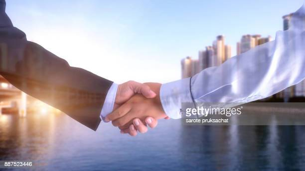 Double exposure of Two businessman shaking hands and city