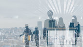 Double exposure of walking business persons and modern cityscape.