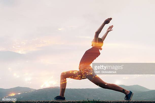 Double exposure of woman doing yoga and city