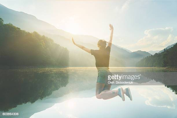 Double exposure of woman jumping and lake