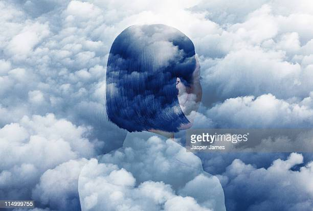 double exposure of woman looking in to clouds