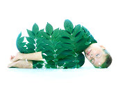 Double exposure portrait of laying girl, combined with photograph of a branch