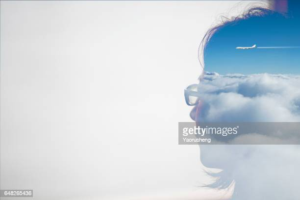 Double exposure portrait of an Asian woman combined with blue sky and aircraft flying over the sky