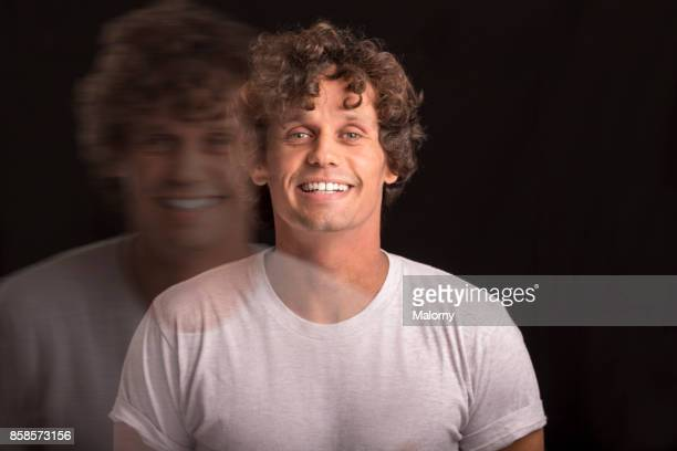 Double Exposure. Portrait of young man with curly hair standing in front of black background, laughing.