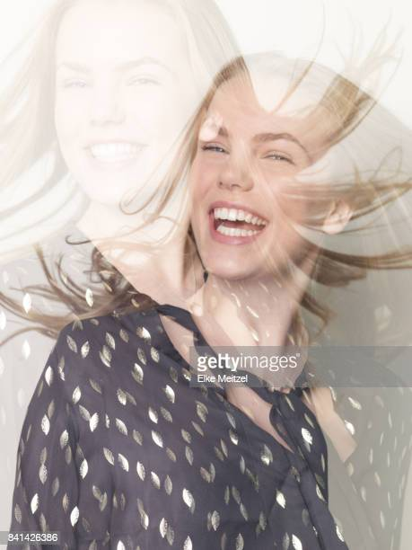 Double exposure portrait of young woman laughing
