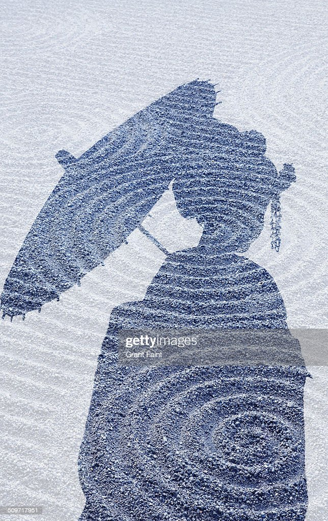Double exposure:Geisha silhouette on sand garden.