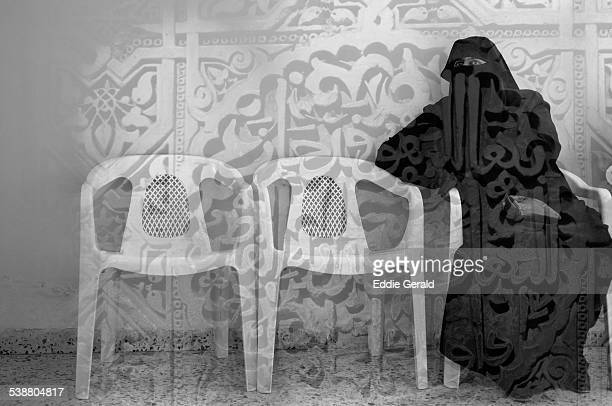 Double expousre combining a veiled muslim woman and relief of verses of Quran from Alhambra in Spain