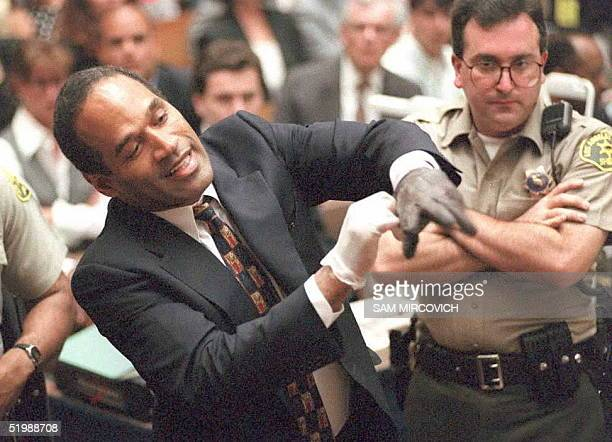 Double murder defendant OJ Simpson puts on one of the bloody gloves as a Los Angeles Sheriff's Deputy looks on during the OJ Simpson murder trial 15...
