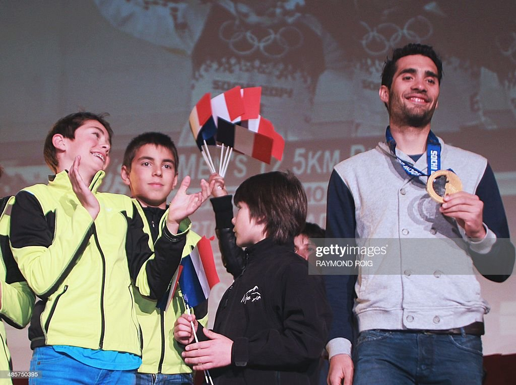 Double Olympic champion biathlete Martin Fourcade (R) poses with his medal during a meeting with his fans in Font-Romeu, in the French Pyrenees, southern France, on April 20, 2014. Fourcade, 25, was cheered by 600 people during a visit in the ski resort where he obtained his first results.