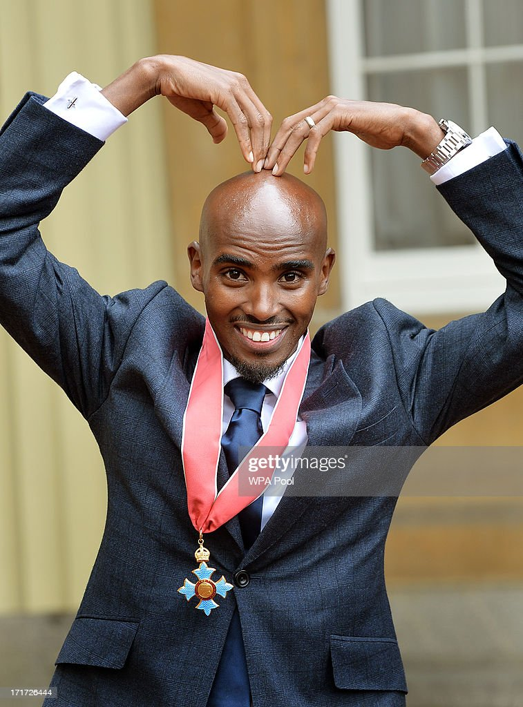 Double Olympic Gold Medal winning athlete Mo Farrah does the 'Mobot' as he wears his CBE after he received the award from Prince Charles, Prince of Wales during an Investiture ceremony at Buckingham Palace on June 28, 2013 in London, England. Mo Farah will receive an CBE for services to Athletics.