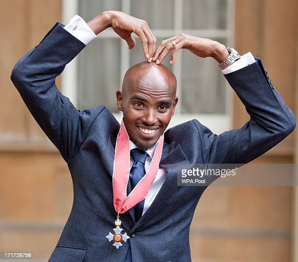 Double Olympic Gold Medal winning athlete Mo Farrah does the 'Mobot' as he wears his CBE after he received the award from Prince Charles Prince of...