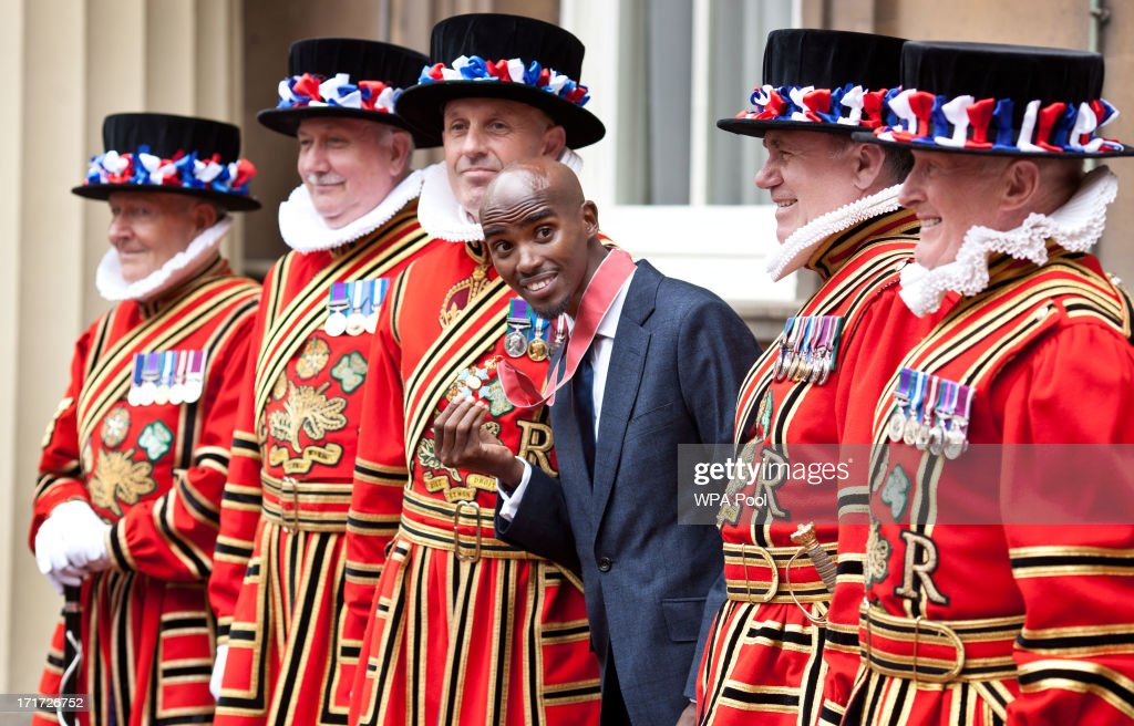 Double Olympic Gold Medal winning athlete Mo Farrah poses with beefeaters as he wears his CBE after he received the award from Prince Charles, Prince of Wales during an Investiture ceremony at Buckingham Palace on June 28, 2013 in London, England. Mo Farah will receive an CBE for services to Athletics.