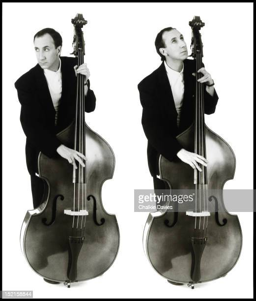 A double portrait of English guitarist Pete Townshend of The Who playing a double bass London November 1985