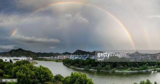 Double rainbow over village .