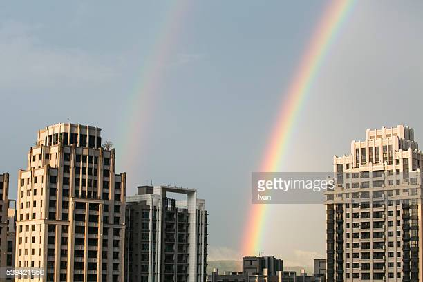 Double Rainbows in A Modern Urban City Against Blue Sky