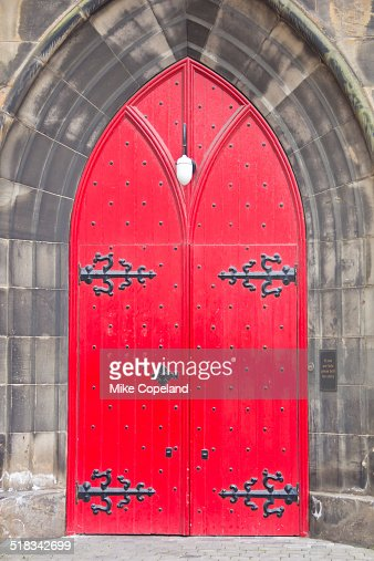 Double red wooden doors with black iron hinges and studs set in a stone arch in the Gothic-styled St Columba's-by-the-Castle Scottish Episcopal Church, Edinburgh, Scotland.
