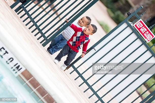 Double trouble! Twin boys try to get into locked pool