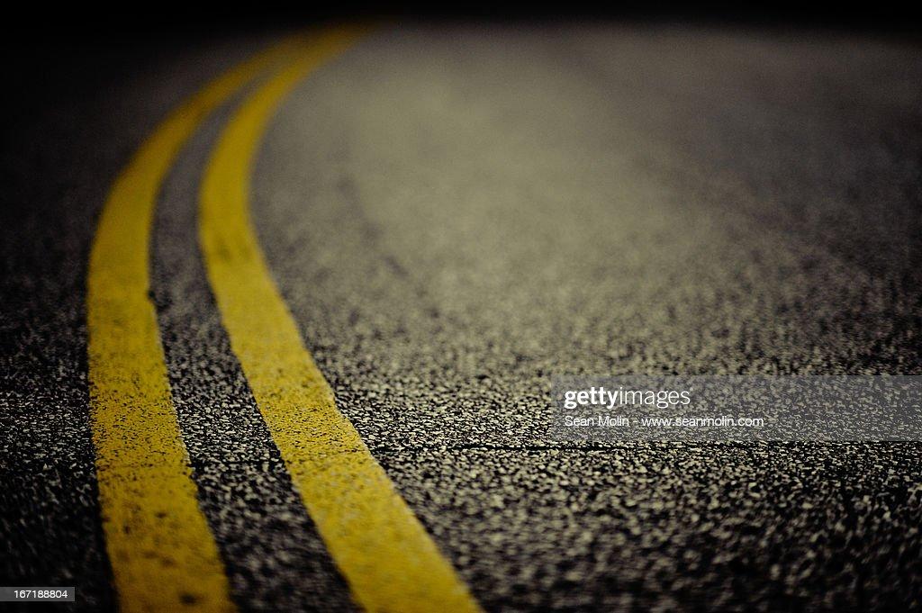 Double yellow line on cracked asphalt