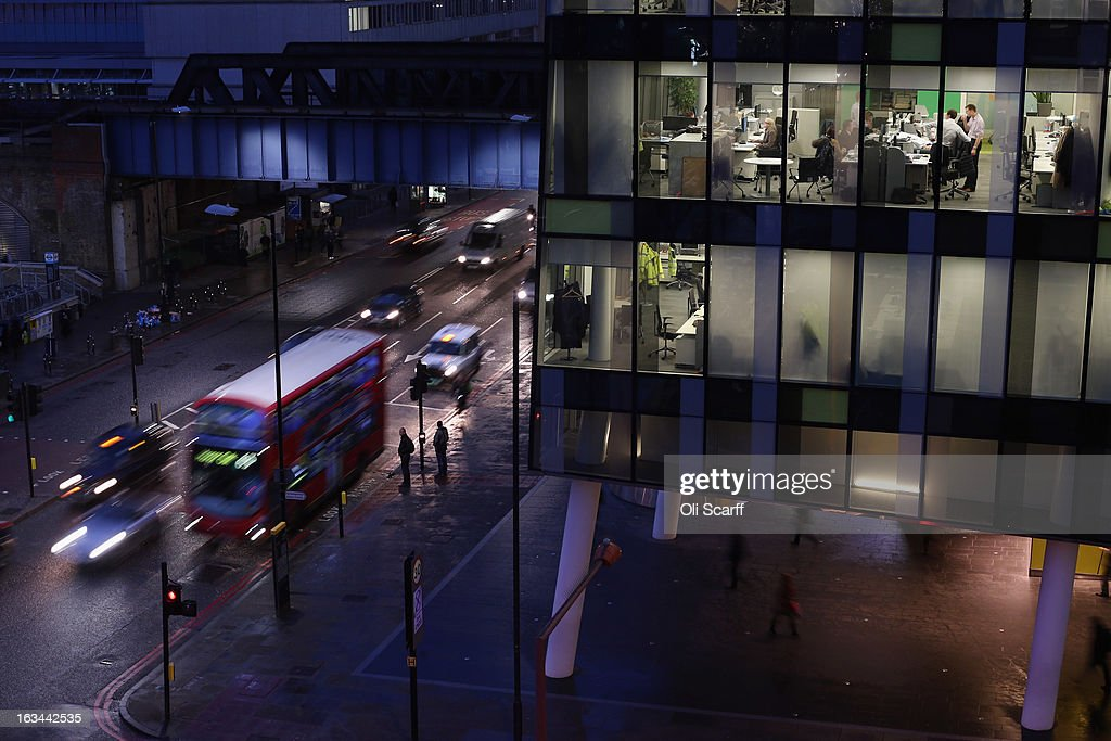 A double-decker bus passes people working in the offices of the Palestra tower, which houses the administration of 'Transport for London,' at dusk on January 28, 2013 in London, England. A recent study of European working hours has shown that British men have the longest working week of any European Union country.