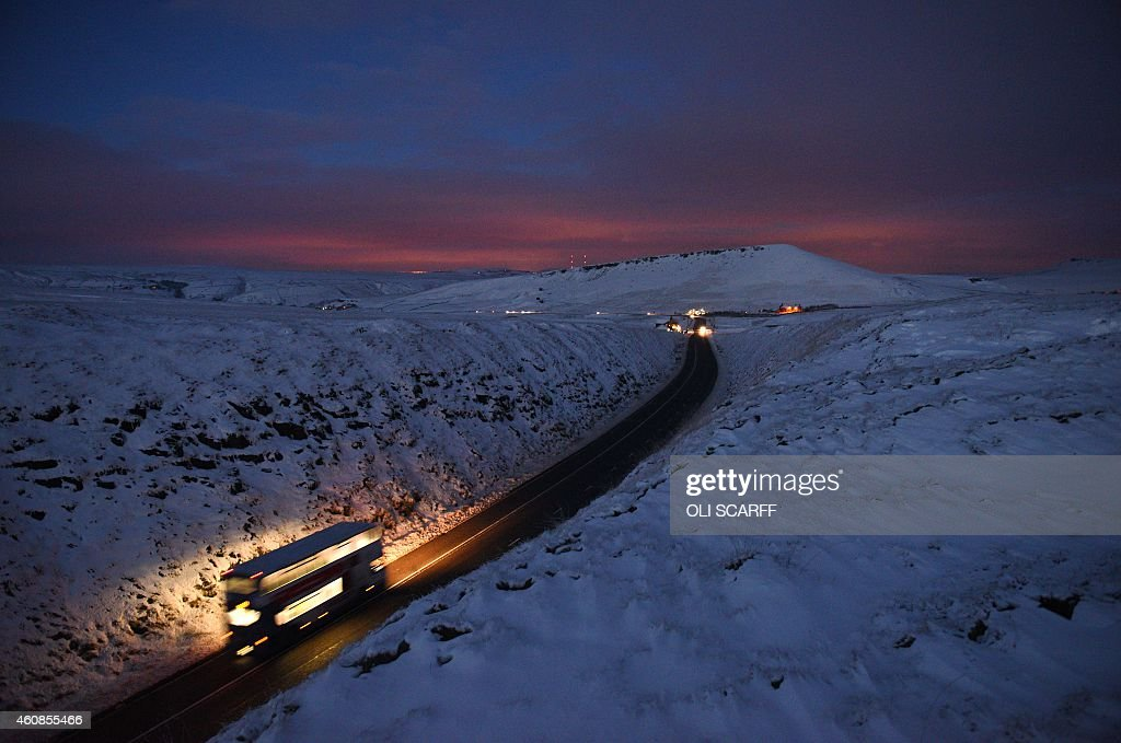 A double-decker bus travels over Standedge between snow-covered fields at dusk near the village of Diggle, northern England, on December 27, 2014. Overnight flurries left parts of Britain blanketed in snow on December 27, causing power shortages and delays at airports.