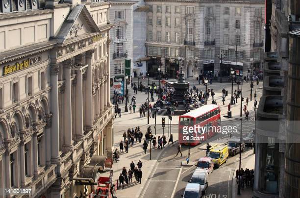 A doubledecker bus travels through Piccadilly Circus on March 19 2012 in London England London's West End is synonymous with theatre productions...