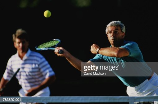 Doubles tennis match, mature man playing forehand volley : Stock Photo